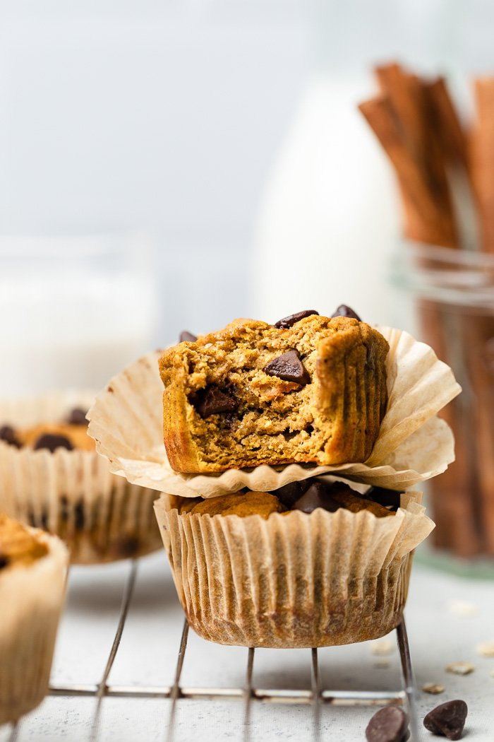 Two healthy pumpkin protein muffins stacked on top of each other with the top one with a bite taken out of it. Behind it more muffins, glass of milk, and cinnamon sticks. They are sitting on a cooling rack.