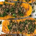 Overhead shot of stuffed butternut squash filled with beef and kale and drizzled with a tahini sauce.