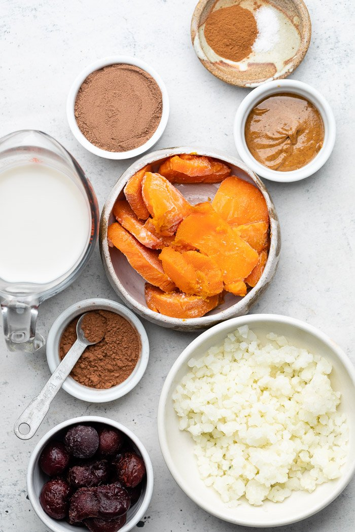 Overhead shot of different bowls filled with frozen sweet potatoes, cauliflower rice, frozen cherries, cup of milk, protein powder, cacao powder, cinnamon, and nut butter.
