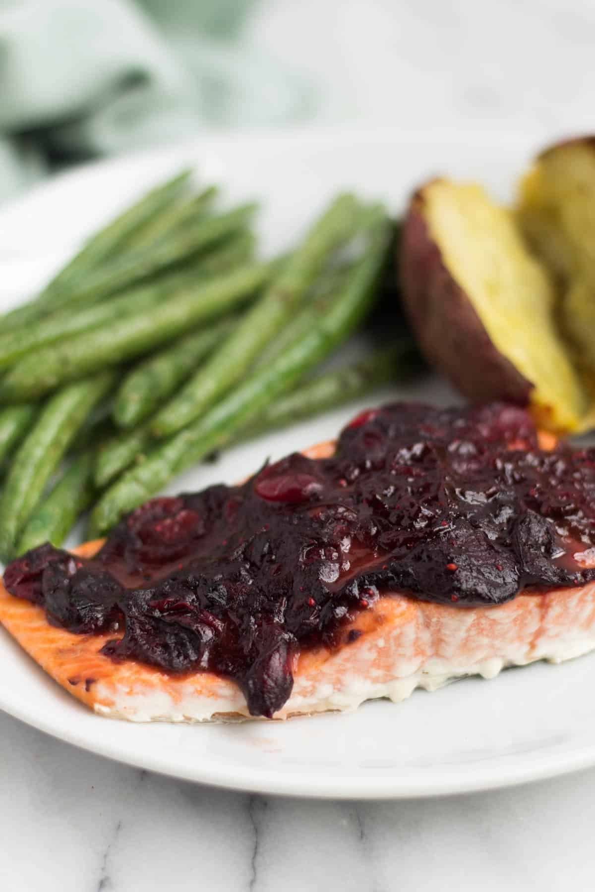 An easy and festive seafood dish, this Cranberry Balsamic Roasted Salmon takes 15 minutes and is a crowd pleaser for the holidays - paleo, gluten free, and Whole30 approved! - Eat the Gain