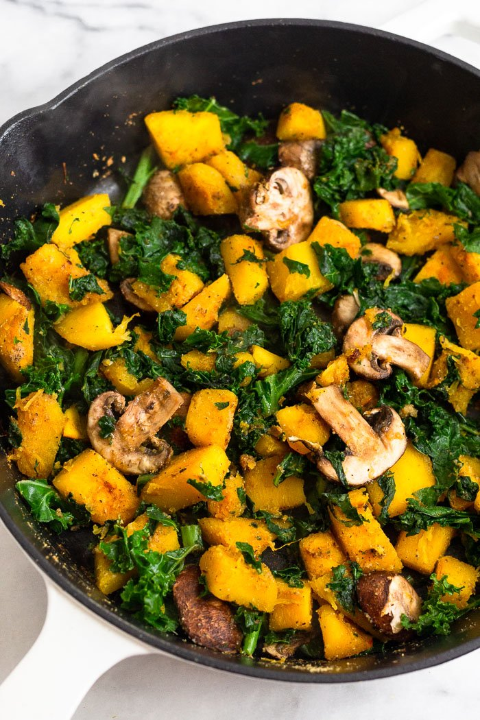 Pan filled with cooked diced pumpkin, kale, mushrooms, and spices.