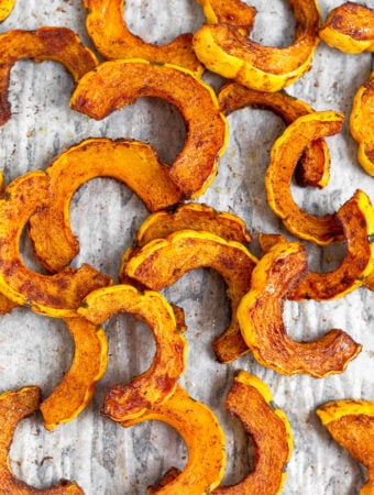 Overhead shot of roasted delicata squash on a baking sheet.
