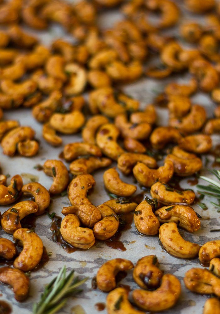 Large sheet pan with rosemary roasted cashews garnished with fresh rosemary.