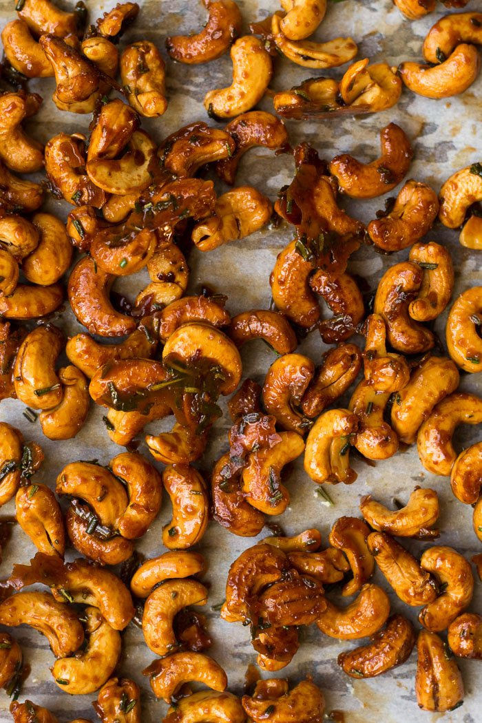 Sheet pan of honey roasted cashews topped with rosemary.