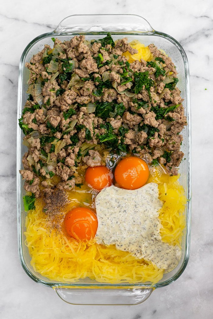 Glass baking dish filled with cooked spaghetti squash, ground turkey and kale, eggs, and ranch dressing before it is mixed up.