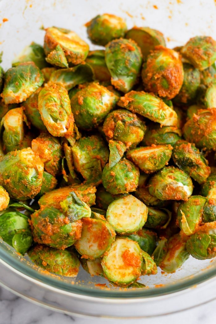 A bowl of brussel sprouts tossed in hot sauce, oil, and spices.