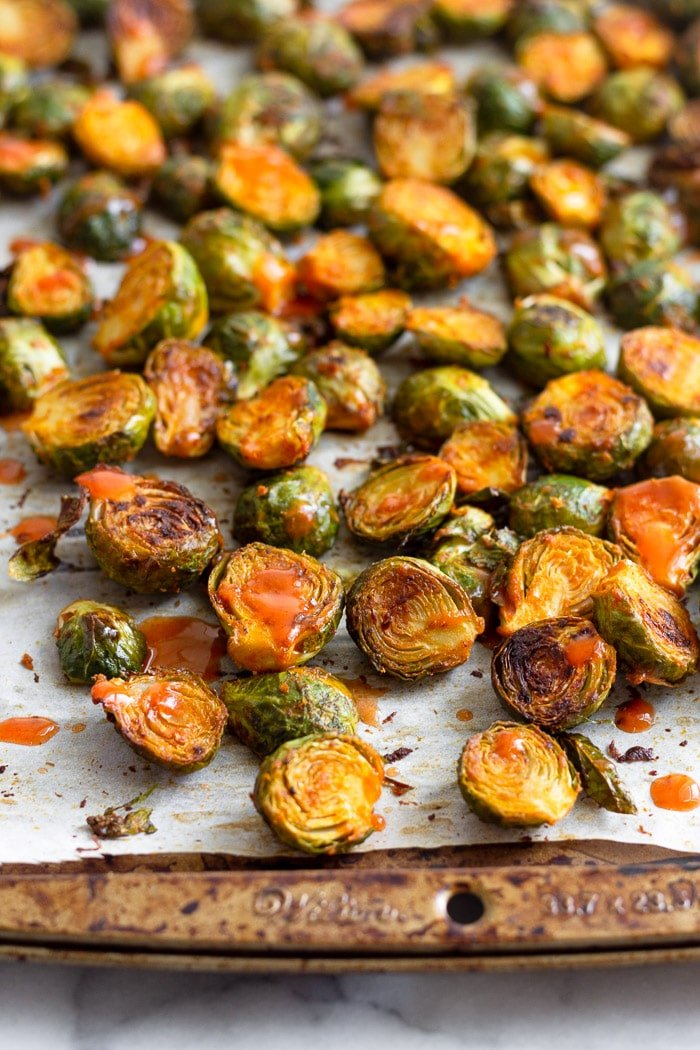 Buffalo roasted brussel sprouts on a baking sheet topped with hot sauce.