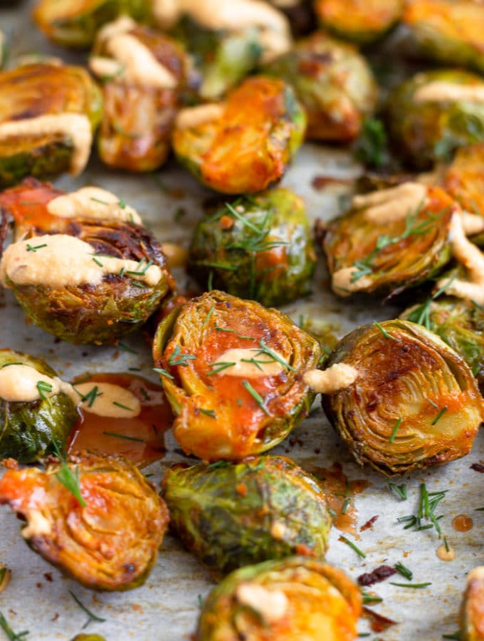 A bunch of buffalo brusssel sprouts topped with cheesy buffalo sauce and fresh dill on a baking sheet.