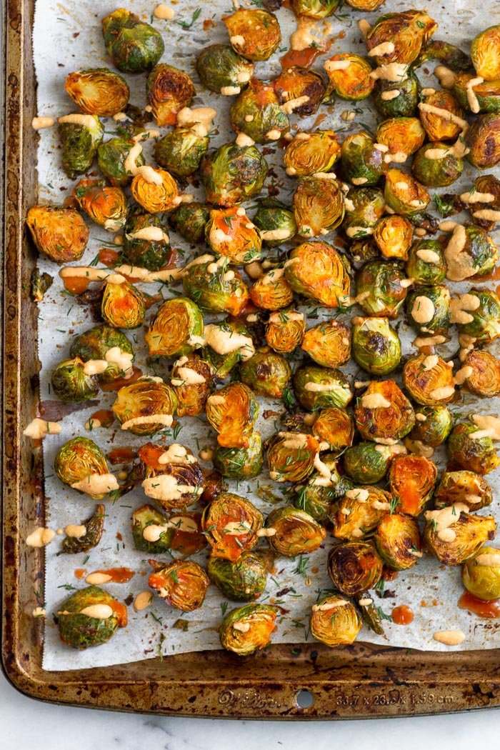 Best sprout recipe topping with fresh dill and cheesy buffalo sauce on a large baking sheet.