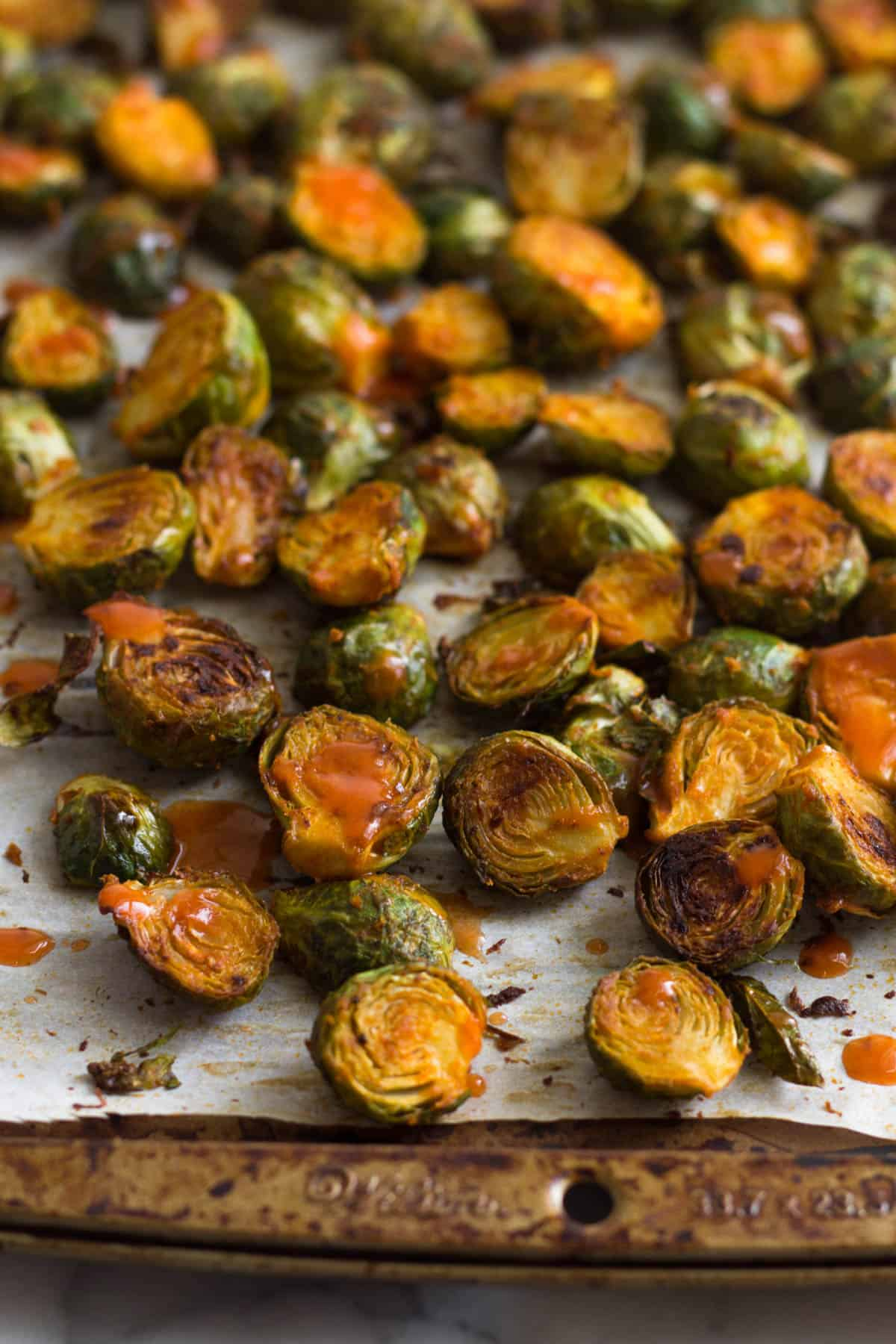 Pan of roasted buffalo brussel sprouts drizzled with hot sauce