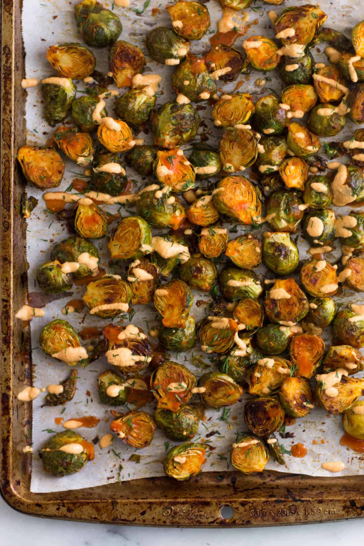Overhead of a pan of roasted cheesy buffalo brussel sprouts.