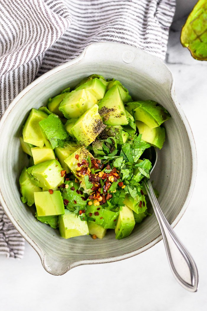 Small bowl of cubed avocado, chopped cilantro, lime juice, and red pepper flakes with a spoon sticking out of it. Next to it is a striped towel and avocado skin.