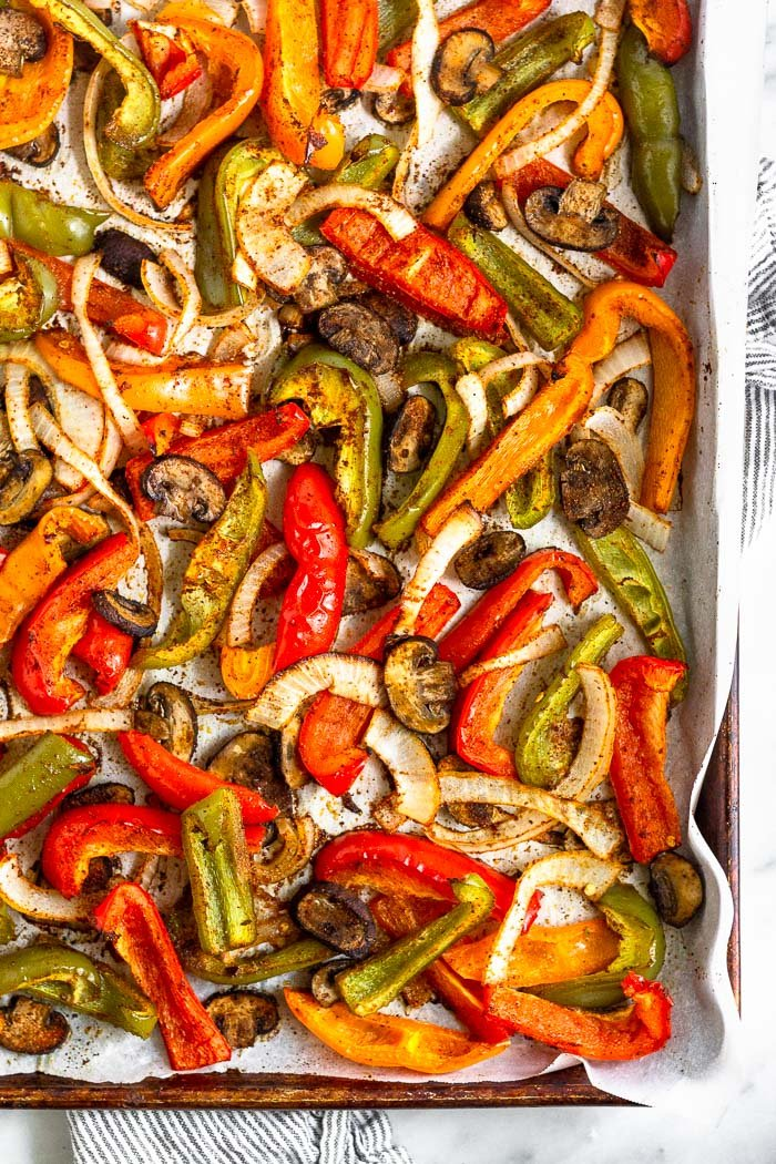 Baking sheet filled with roasted peppers, onions, and mushrooms.