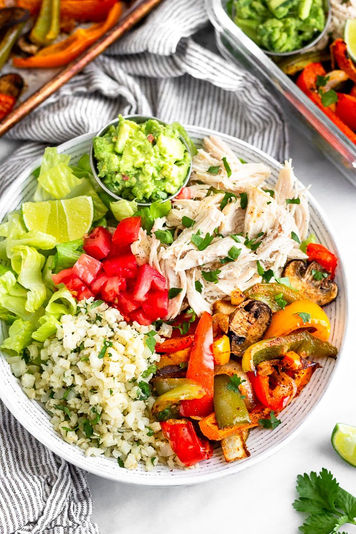 Low carb chicken burrito bowl filled with cauliflower rice. lettuce. chicken, and veggies. It is garnished with a lime wedge and a side of guacamole. Behind it is a container fill with another burrito bowl and a pan of roasted veggies.
