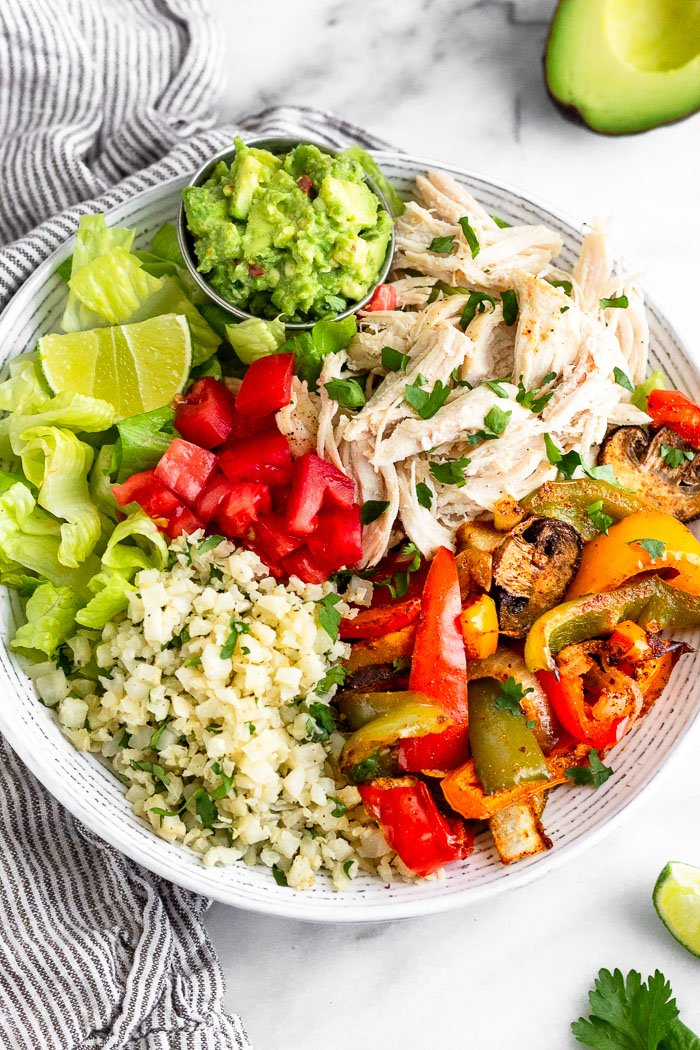 Chicken burrito bowl filled with shredded chicken, fajita veggies. cilantro lime cauliflower rice, diced tomatoes, chopped romaine, guacamole, and lime wedge. Next to it is a striped towel, half and avocado, and some cilantro and a lime wedge.