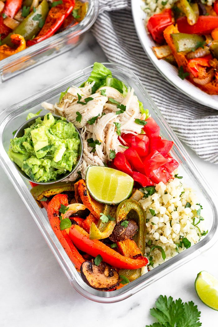 Glass meal prep container filled with a paleo chicken burrito bowl. Behind it is a plate of fajita veggies and another meal prep container.