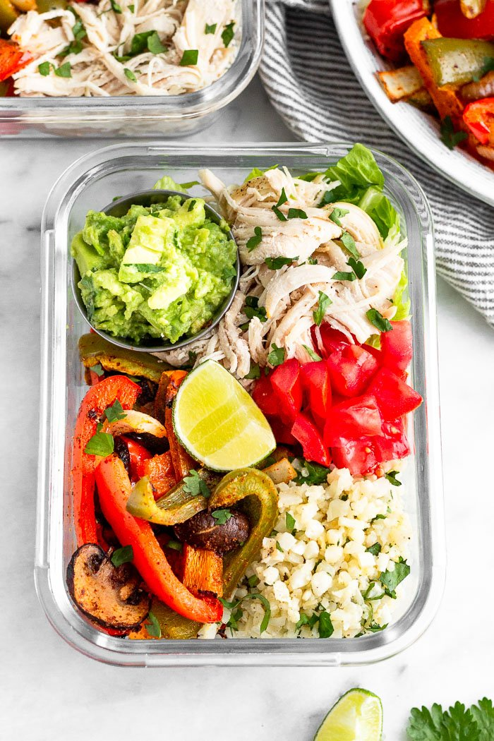 Meal prep chicken burrito bowl in a glass container with fajita veggies, cauliflower rice, tomatoes, shredded chicken, lettuce, lime wedge, and container of mashed avocado. Behind it is another bowl and a plate of more veggies.
