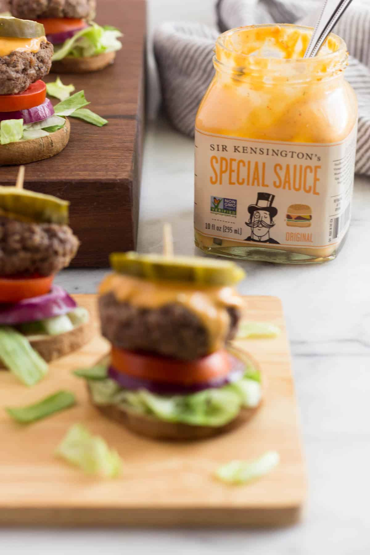 Burger slider on a sweet potato bun that is out of focus with a jar of special sauce that is in focus in the background