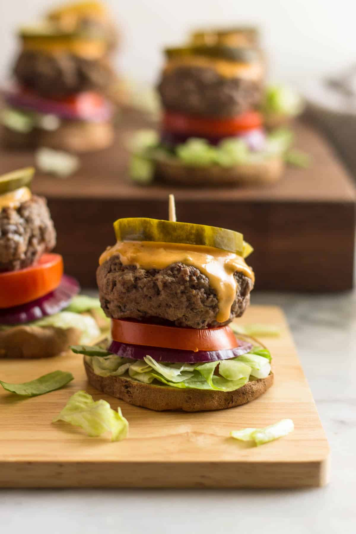 Close up of a burger slider on a sweet potato bun on a wooden board with a lot of sliders in the background on a butcher block