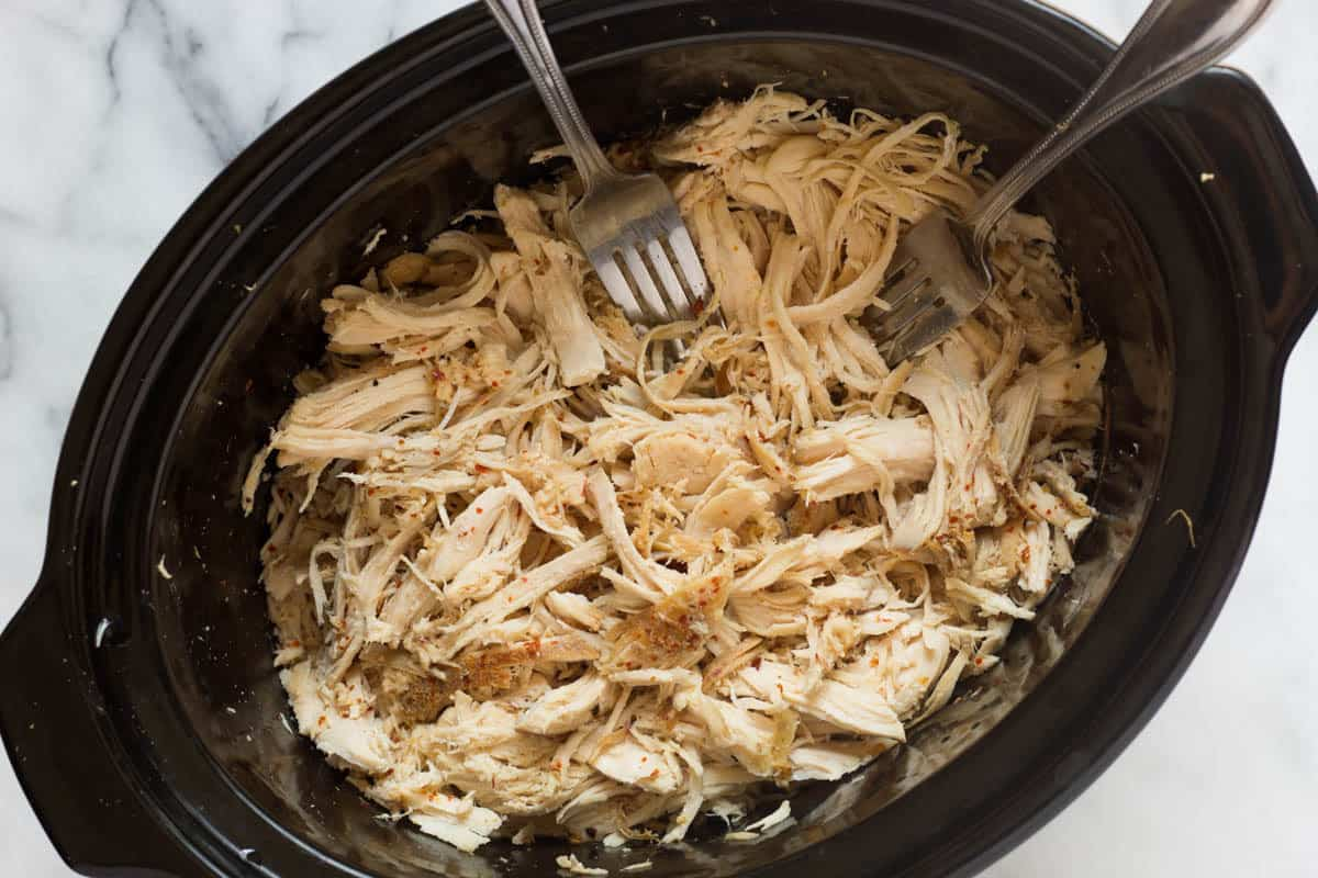 How to make Easy Shredded Chicken 2 ways - in a slow cooker or Instant Pot and only 3 ingredients - will be a meal prep staple in your household for easy & healthy protein packed meals - gluten/dairy free, paleo, & Whole30. Plus a free guide on meal prep + 5 different meals to repurpose it throughout the week! - Eat the Gains #mealprep #Whole30 #mealplanning #shreddedchicken