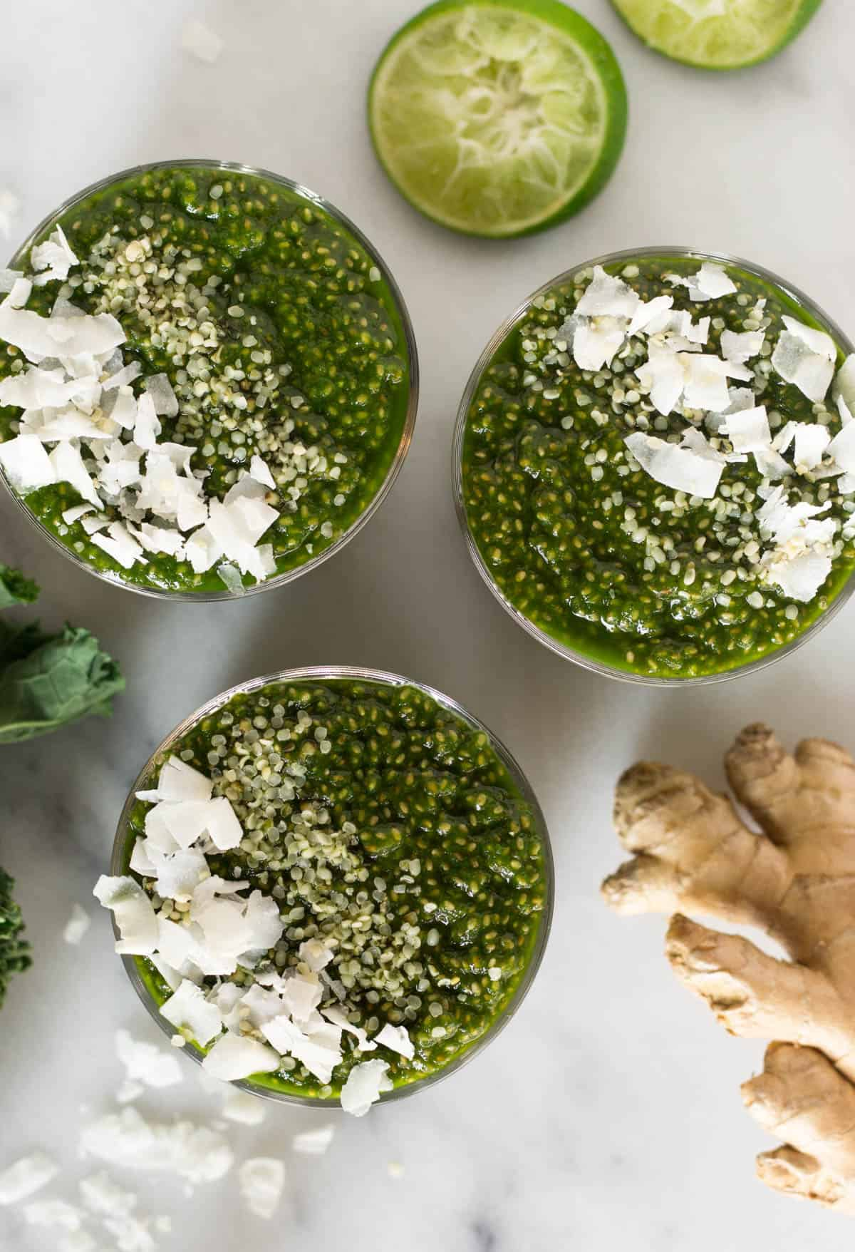 Overhead of 3 glasses of green juice chia puddings, ginger, and limes