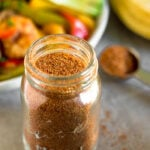 Healthy homemade taco seasoning in a glass jar with a teaspoon behind it filled with seasoning and a plate of fajitas.