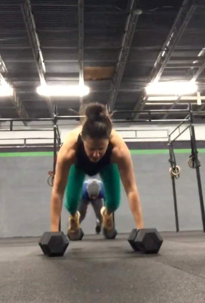girl holding dumbbells doing a burpee