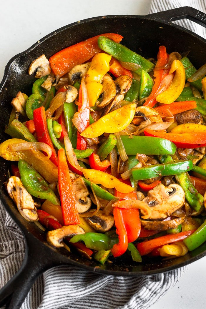 Cast iron of sautéed peppers, onions, and mushrooms.