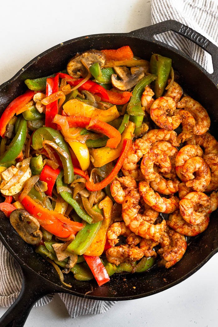 Large cast iron filled with sautéed peppers, onion, and mushrooms with cooked shrimp to make one pan shrimp fajitas.