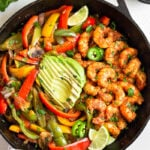Cast iron skillet filled with shrimp fajitas and topped with sliced avocado. Around it is cilantro, half an avocado, bowl of salsa, and a bowl of limes.