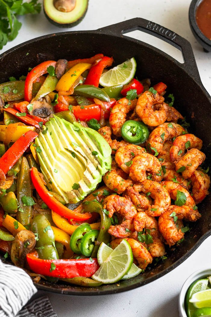 Whole30 shrimp fajita recipe topped with sliced avocado. Around it is cilantro, lime wedges, salsa, and half an avocado.