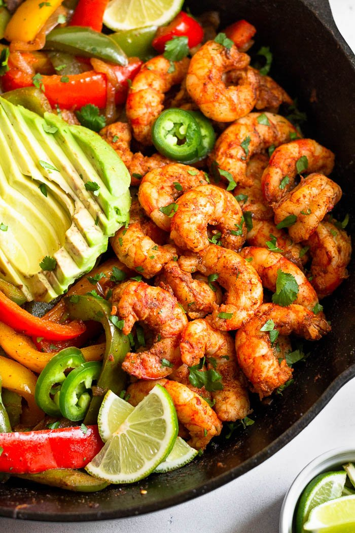 Close up Whole30 shrimp recipe. Shrimp is cooked in taco seasoning with sautéed onions, peppers, and mushrooms next to it. It is all topped with avocado.