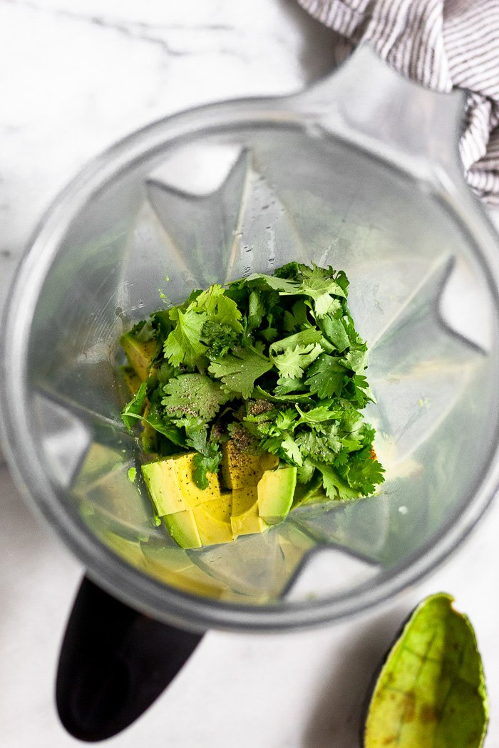 Blender filled with avocado, cilantro, and salt and pepper.