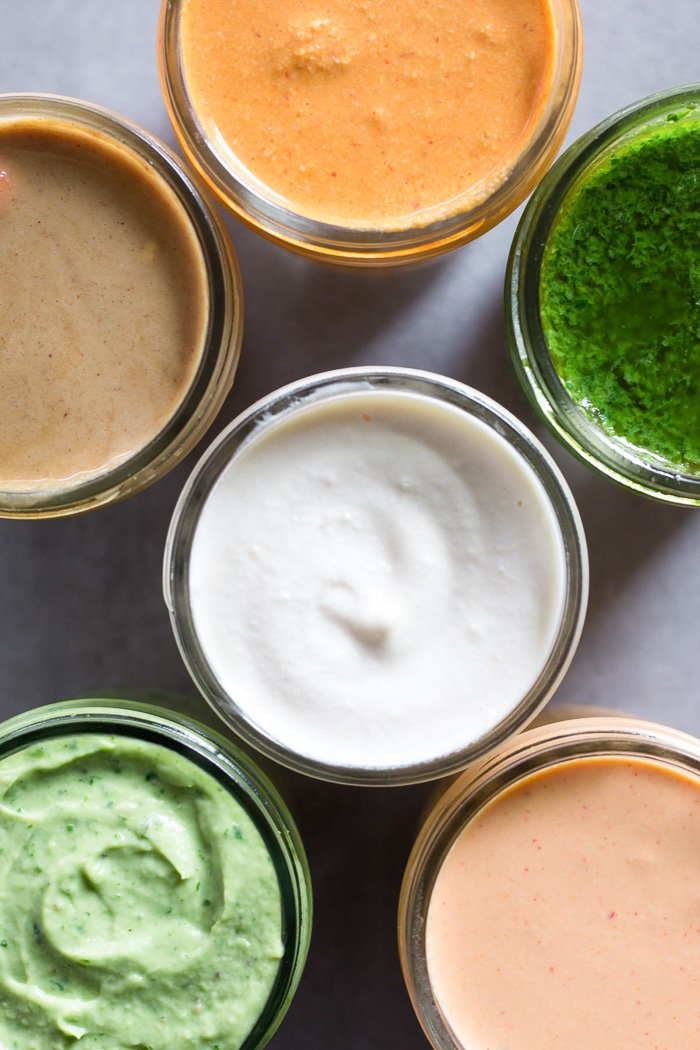 Overhead shot of a close up of 6 jars filled with different sauces in each.