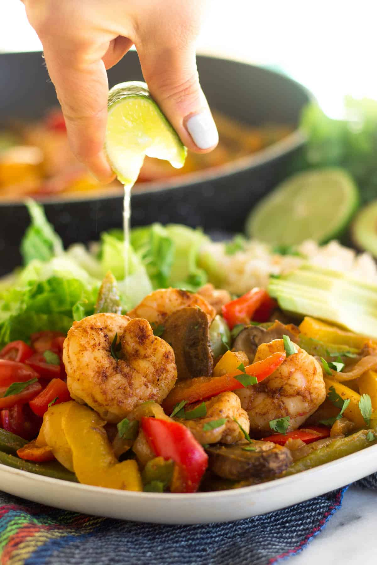 Close of a plate with shrimp fajitas and a person squeezing lime juice on them. Background is a pan of shrimp fajitas.