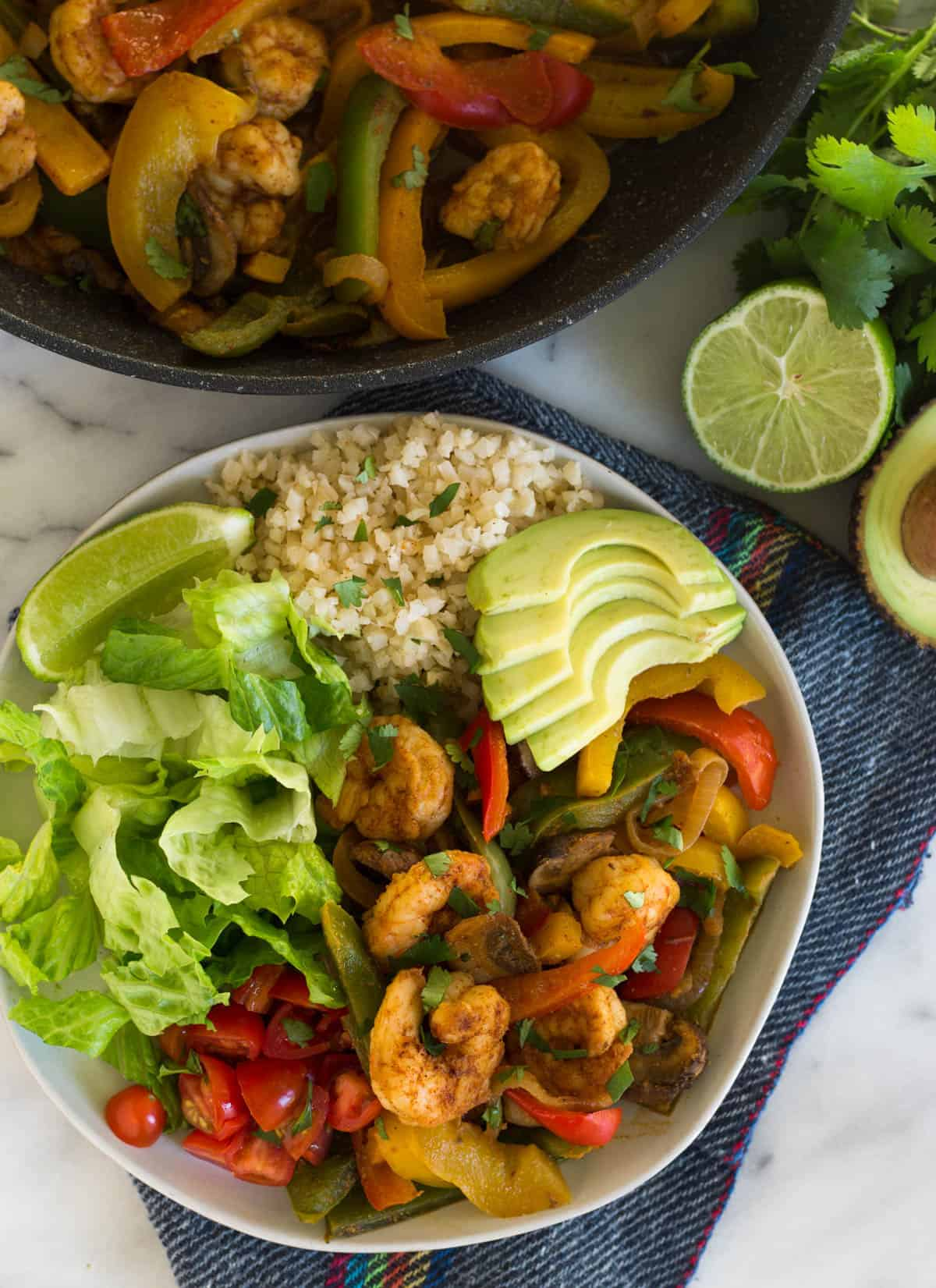 overhead of a plate with shrimp fajitas, lettuce, tomatoes, cauliflower rice, and avocado with a pan of shrimp fajitas and an avocado and lime