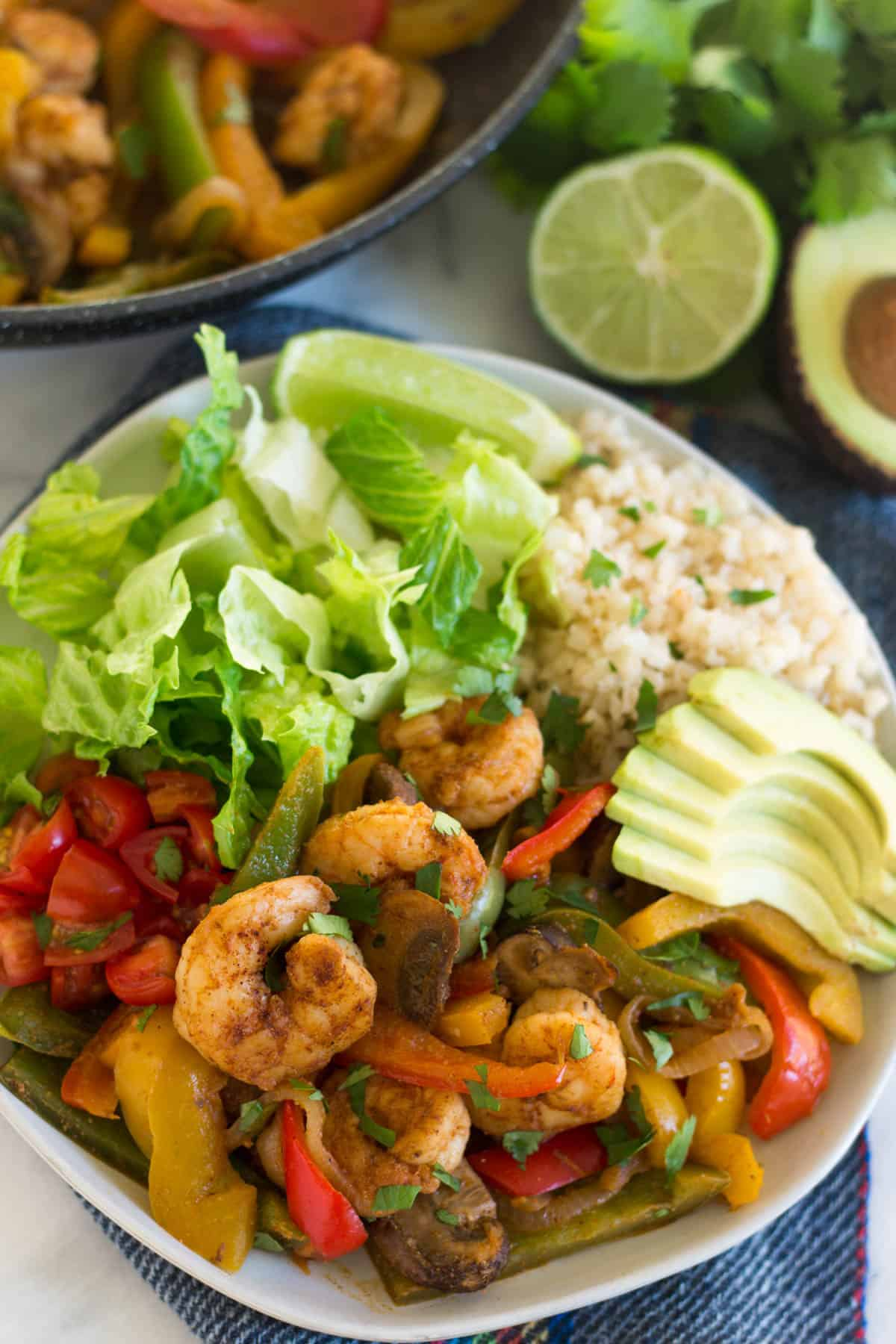 White plate of shrimp fajitas and sides with a pan , avocado, and lime in the background