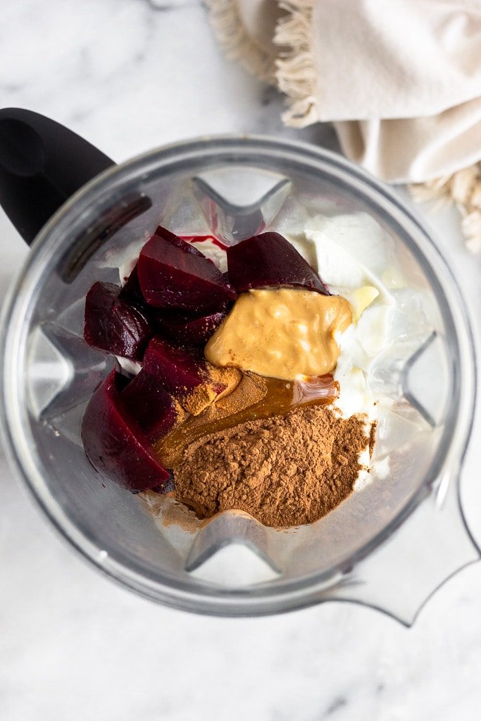 Blender filled with greek yogurt, beets, cacao powder, cashew butter, cinnamon, and honey make a smoothie.