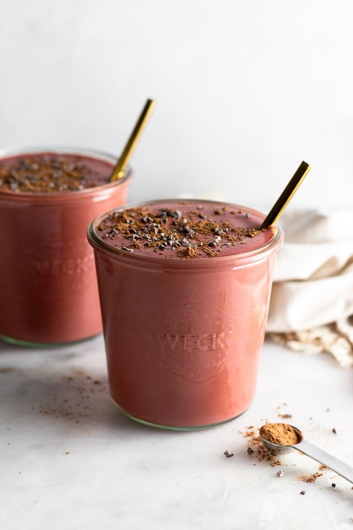 High protein smoothie with beets, greek yogurt, and chocolate in two jars with straws coming out of them.