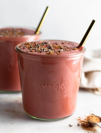 Two chocolate beet smoothies in jars topped with cacao nibs and gold straws in them. In front of them is a teaspoon filled with cacao powder and behind them is a tan linen.