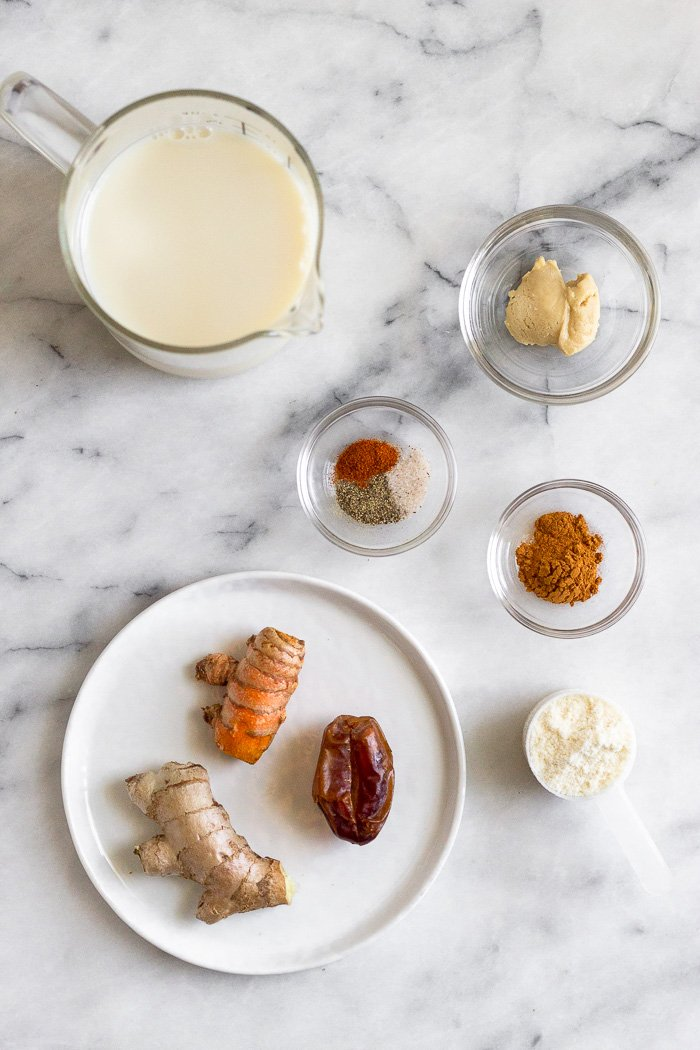 Overhead shot of a cup of milk, small dish of cashew butter, two small bowls of spices, a scoop of protein powder, and a plate with fresh ginger, fresh turmeric, and a date.