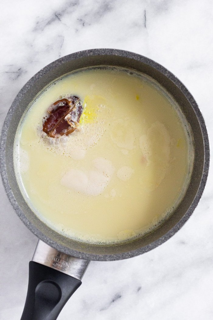 A pot filled with milk with a date and fresh ginger and turmeric. The milk is slightly yellow.