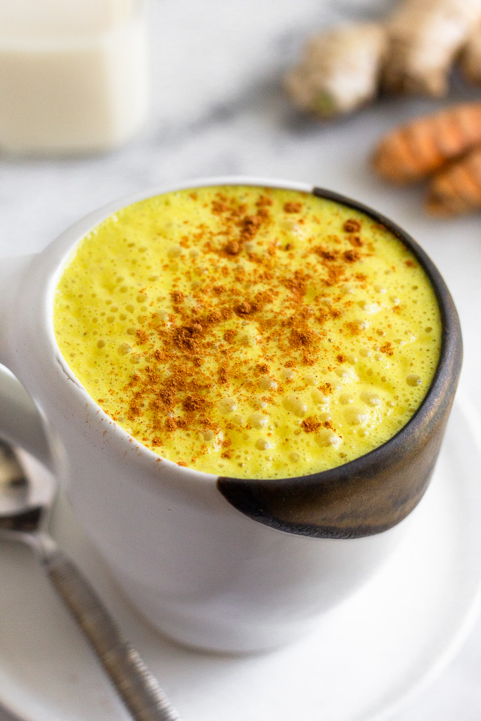 Golden milk turmeric latter sprinkled with cinnamon in a mug.