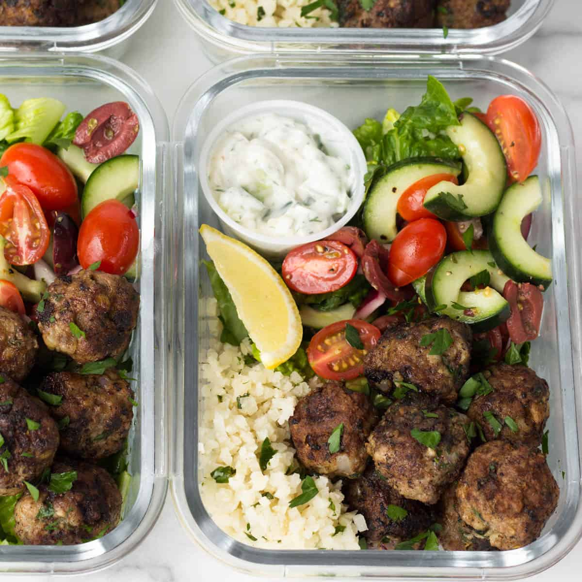 Close up of a few meal prep Whole30 Greek lamb meatball bowls