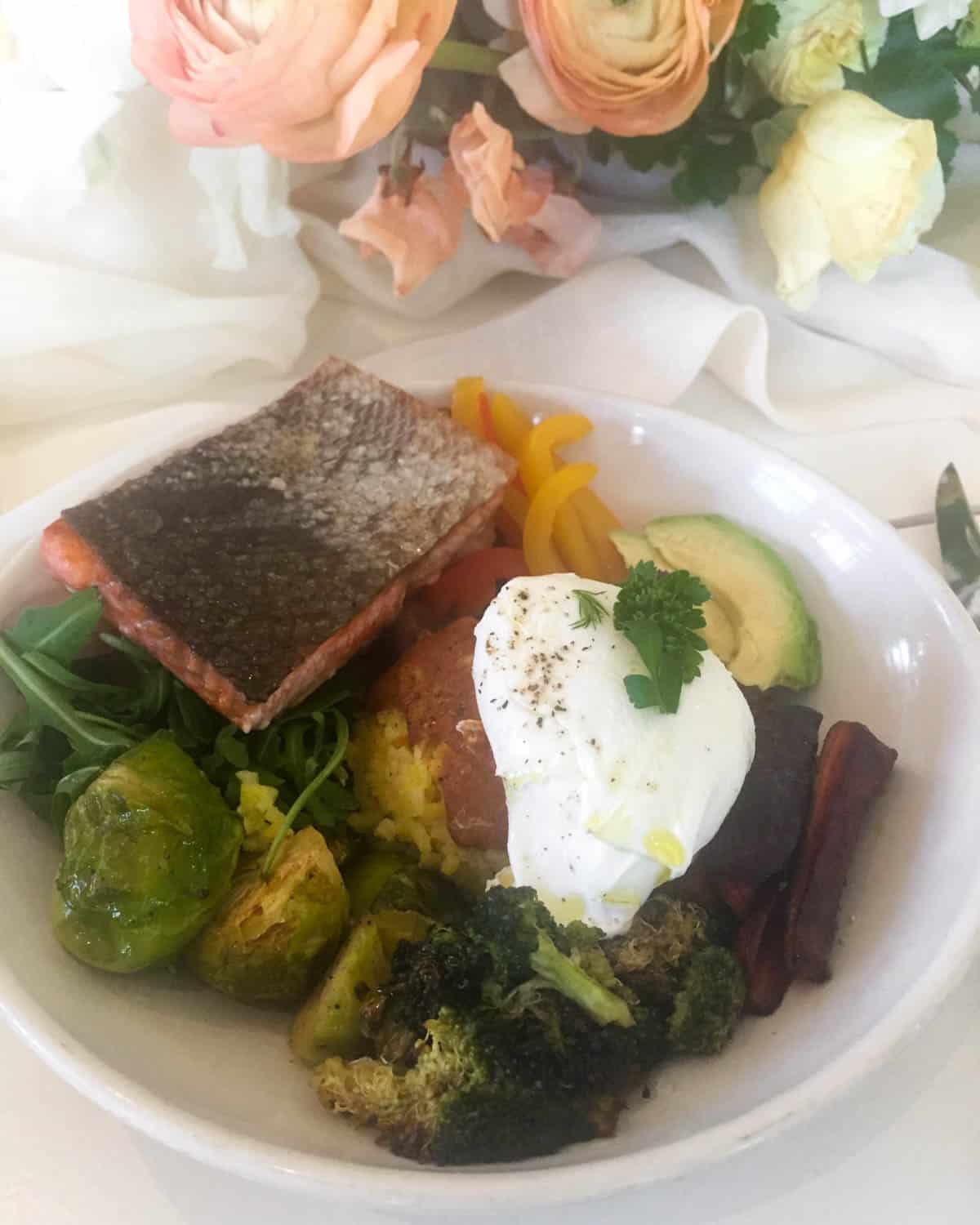 Bowl of roasted salmon, veggies, rice, avocado, and a poached egg on top