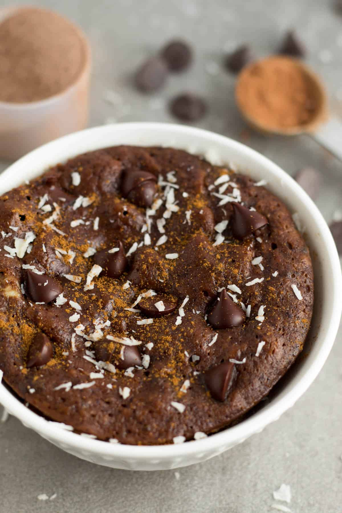 Paleo Healthy Chocolate Protein Mug Cake sprinkles with cinnamon and coconut with a teaspoon of cacao powder, chocolate chips, and powder powder in the background.