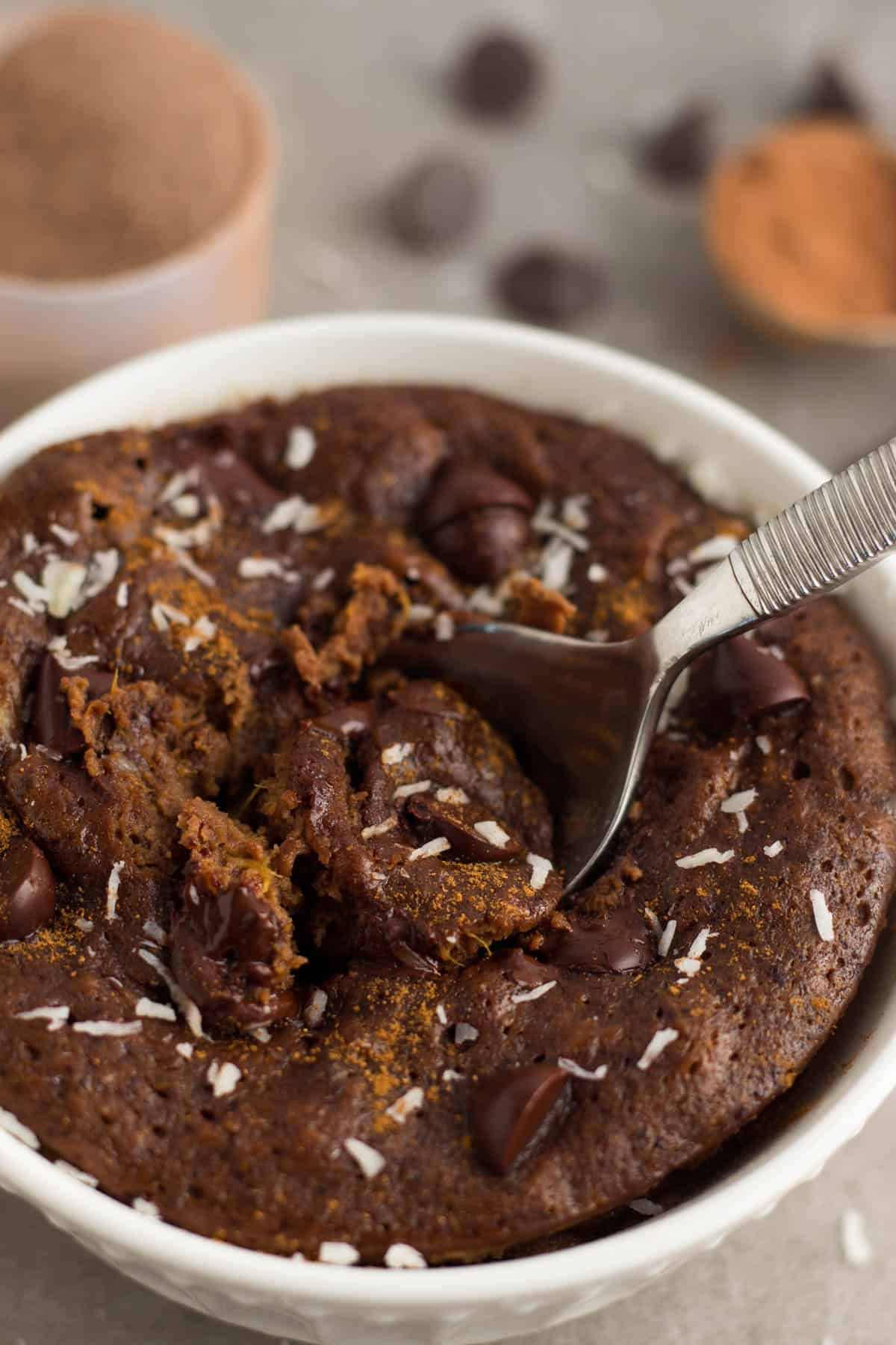 A spoon digging into a healthy chocolate protein mug cake topped with cinnamon and coconut
