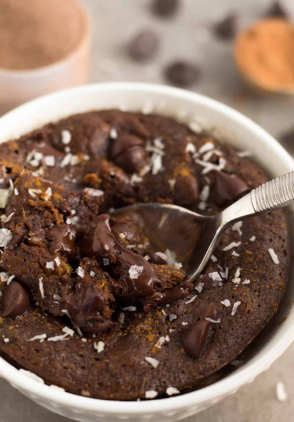 Spoon taking out a scoop of a healthy chocolate protein mug cake with melted chocolate chips.
