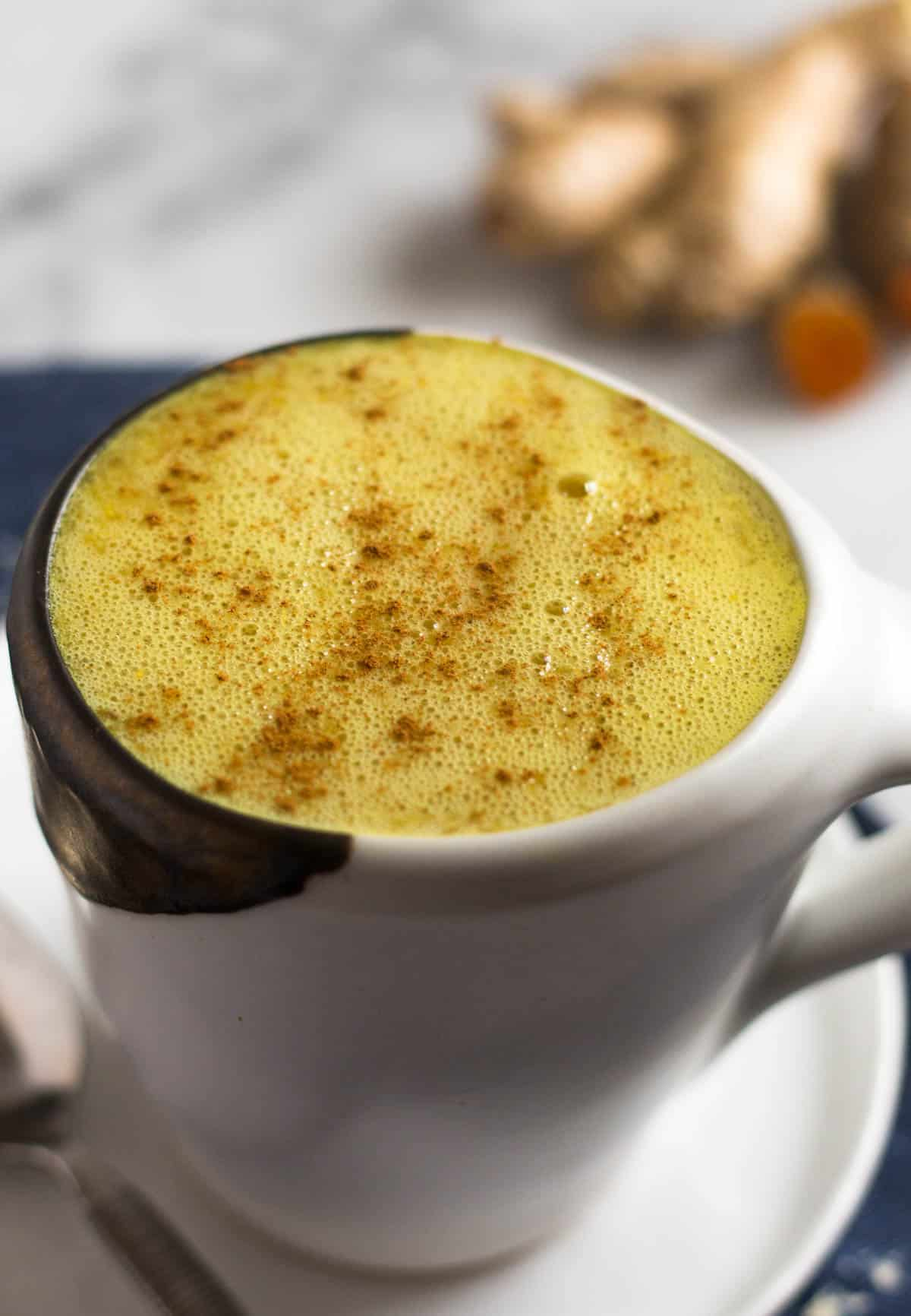White mug with a warm golden milk turmeric latte with cinnamon sprinkled on top