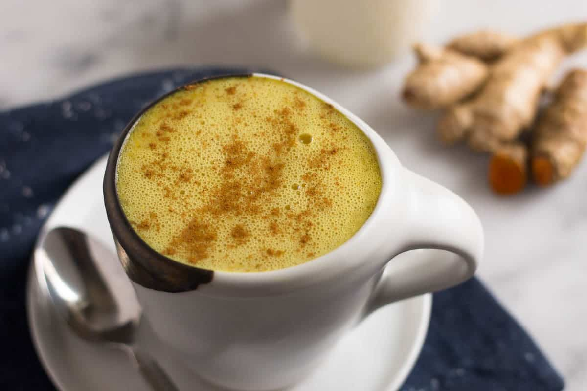 Golden milk turmeric latte in a shite mug with a plate and a spoon and fresh ginger, turmeric, and almond milk in the background